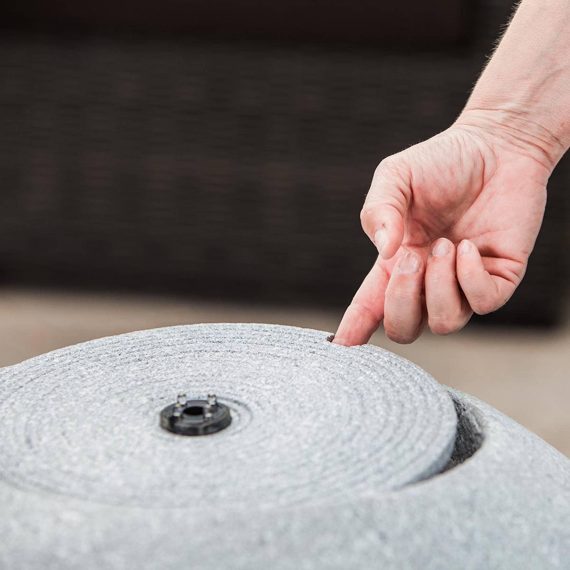Hand hebt Deckel von grauem runden Gartenbrunnen