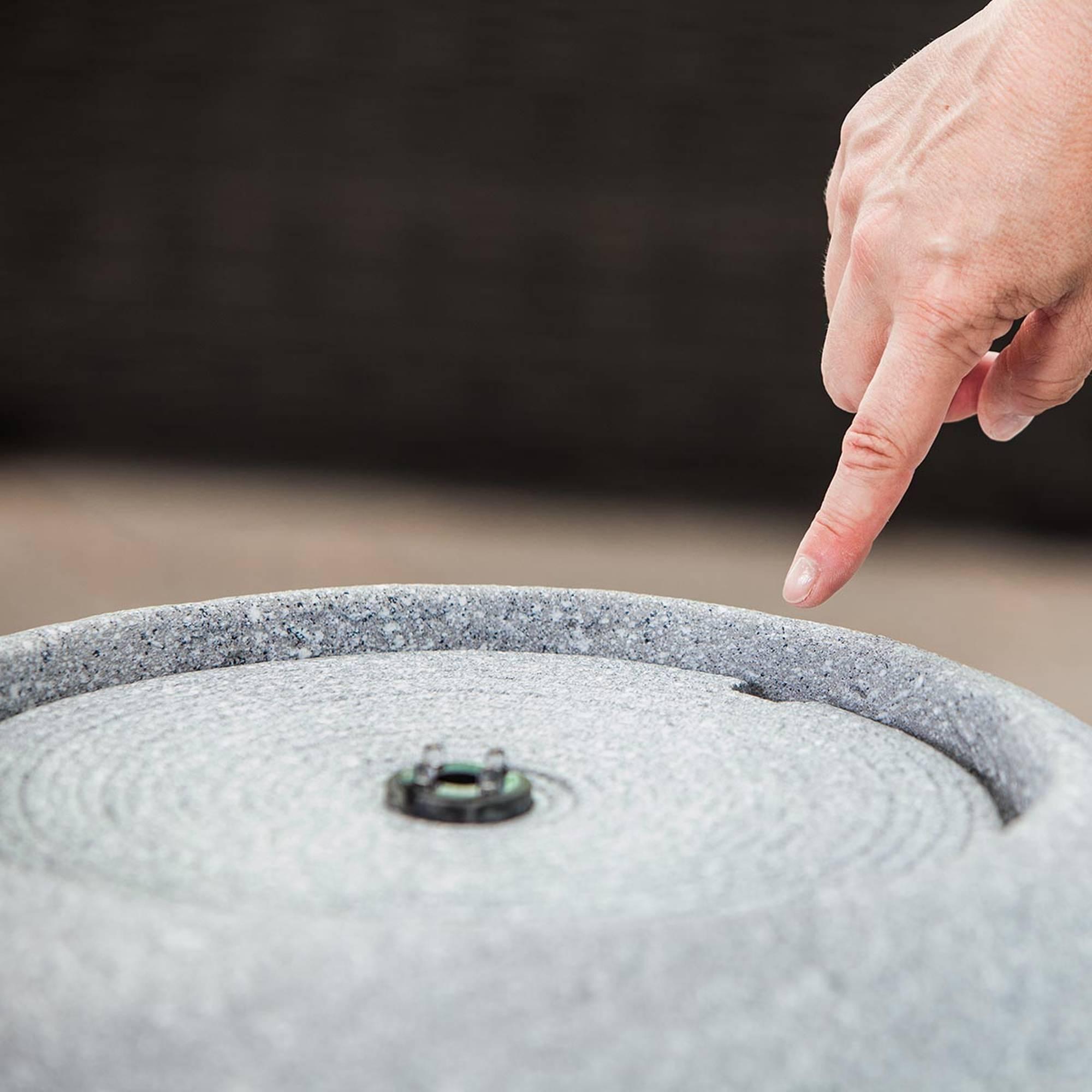 grauer runder Gartenbrunnen mit flachem Deckel und Beleuchtungsring