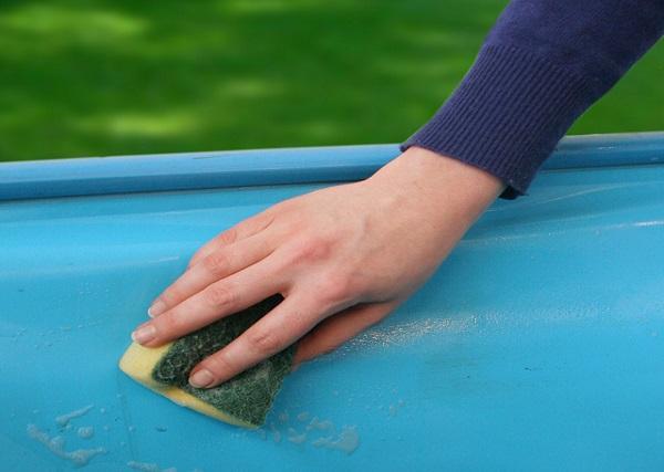 Person reinigt Beckenwand mit Schwamm